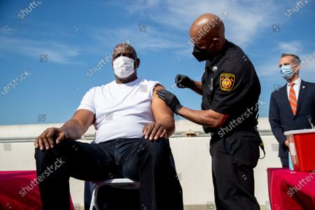 Los Angeles Fire Chief Ralph Terrazas gives a vaccine shot to Magic Johnson on the rooftop of parking structure at USC as a part of a vaccination awareness event at USC on March 24, 2021 in Los Angeles, California.(Gina Ferazzi / Los Angeles Times)