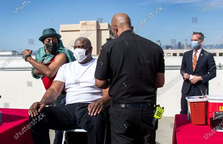 Arsenio Hall shows off his muscles to Magic Johnson before they both get a vaccine from Los Angeles Fire Chief Ralph Terrazas on the rooftop of parking structure at USC as a part of a vaccination awareness event at USC on March 24, 2021 in Los Angeles, California. L.A. Mayor Eric Garcetti is in the background. (Gina Ferazzi / Los Angeles Times)