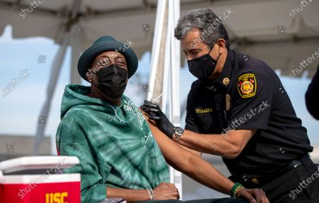 Los Angeles Fire Chief Ralph Terrazas gives a vaccine shot to Arsenio Hall on the rooftop of parking structure at USC as a part of a vaccination awareness event at USC on March 24, 2021 in Los Angeles, California.(Gina Ferazzi / Los Angeles Times)