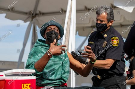 Arsenio Hall reacts after getting a vaccine shot from Los Angeles Fire Chief Ralph Terrazas on the rooftop of parking structure at USC as a part of a vaccination awareness event at USC on March 24, 2021 in Los Angeles, California. He said it felt good. (Gina Ferazzi / Los Angeles Times)