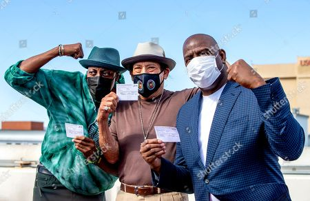 US actors Arsenio Hall and Danny Trejo, and former NBA player Magic Johnson pose for a photo after they all got vaccine shots on the rooftop of a parking structure as a part of a vaccination awareness event at USC in Los Angeles