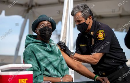 US actor Arsenio Hall receives a COVID-19 vaccine shot from Los Angeles Fire Chief Ralph Terrazas on the rooftop of parking structure as a part of a vaccination awareness event at USC in Los Angeles, California, 24 March 2021.