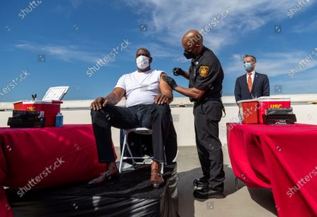 Los Angeles Fire Department Capt. Kairi Brown gives a vaccine shot to former Los Angeles Lakers NBA basketball star Magic Johnson on the rooftop of a parking structure at the University of Southern California as a part of a vaccination awareness event at USC, in Los Angeles