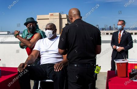 Arsenio Hall shows off his muscles to Magic Johnson before they both get a COVID-19 vaccination from Los Angeles Fire Department Capt. Kairi Brown on the rooftop of parking structure at the University of Southern California as a part of a vaccination awareness event at USC, in Los Angeles. Los Angeles Mayor Eric Garcetti is in the background, at right