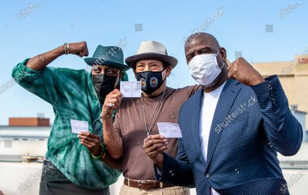 Arsenio Hall, left, Danny Trejo and Magic Johnson pose for a photo after they all got COVID-19 vaccine shots on the rooftop of a parking structure at the University of Southern California as a part of a vaccination awareness event at USC, in Los Angeles