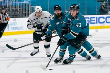 San Jose Sharks left wing John Leonard (43) skates in front of defenseman Brent Burns (88) and Los Angeles Kings center Trevor Moore (12) during the first period of an NHL hockey game in San Jose, Calif