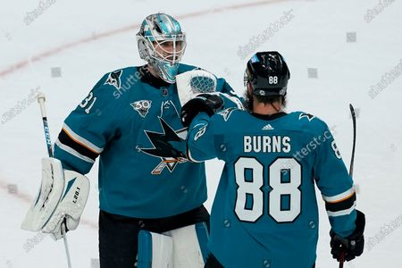 San Jose Sharks goaltender Martin Jones, left, celebrates with defenseman Brent Burns (88) after the Sharks defeated the Los Angeles Kings in an NHL hockey game in San Jose, Calif