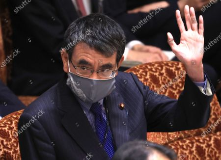 Japanese Administrative Reform Minister Taro Kono raises his hand to answer a question at Upper House's budget committee session at the National Diet in Tokyo on Thursday, March 25, 2021.