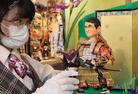 Japanese doll maker Kyugetsu employee displays a samurai doll of Japanese Administrative Reform Minister Taro Kono who is in charge of vaccination for the new coronavirus at the company's showroom in Tokyo on Thursday, March 25, 2021 to celebrate Children's Day on May 5. In Japanese tradition, parents decorate samurai dolls to wish their children may grow up to be health and robust.