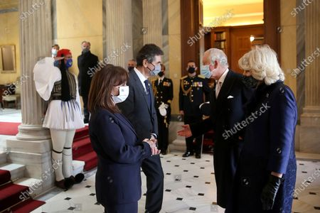 Greek President Katerina Sakellaropoulou, left, and her partner Pavlos Kotsonis, second left, welcome Britain's Prince Charles Charles, second right, and and his wife Camilla, the Duchess of Cornwall at the Presidential Palace in Athens, . Greece's celebrations for the bicentenary of the start of the nation's war of independence are culminating in a military parade and warplane flyby in Athens on Thursday, the country's Independence Day