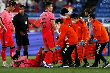 Stock Image of South Korea's Jung Woo-young, bottom left, waits to be carried on stretcher after his injury during their friendly soccer match against Japan at Nissan Stadium in Yokohama, Japan