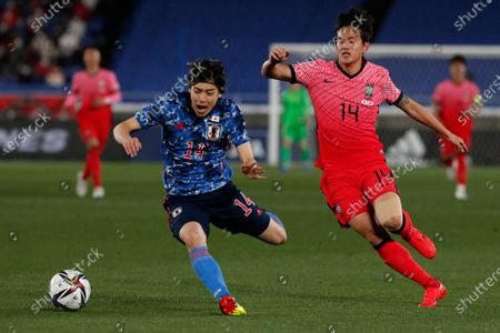 Japan's Junya Ito, left, and South Korea's Hong Chul vie for the ball during their friendly soccer match at Nissan Stadium in Yokohama, Japan