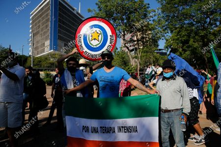 """Member of the Coordinator of Peasant and Indigenous Workers organization holds a flag covered by the Spanish message """"For an Intensive Care Unit"""" during a protest calling for the resignation of President Mario Abdo Benitez over his handling of the coronavirus pandemic and the state of the public health system in Asuncion, Paraguay"""
