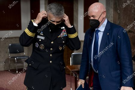 U.S. Cyber Command head, National Security Agency Director and Central Security Service Chief Gen. Paul Nakasone, left, and United States Senator Mark Kelly (Democrat of Arizona)., right, speak following a hearing to examine United States Special Operations Command and United States Cyber Command in review of the Defense Authorization Request for fiscal year 2022 and the Future Years Defense Program, on Capitol Hill,, in Washington.