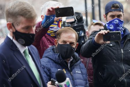 Reporters listen as Boulder County, Colo., District Attorney Michael Dougherty, front, speaks after a hearing for the suspect in the mass shooting at a grocery store, outside the justice center in Boulder, Colo