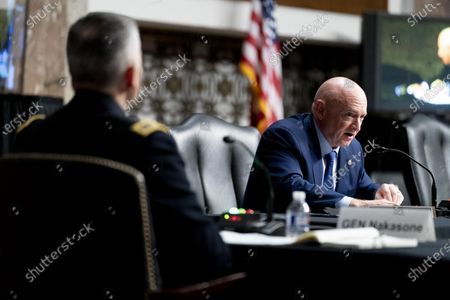 Cyber Command Commander, National Security Agency Director and Central Security Service Chief, Gen. Paul Nakasone (L) appears as Sen. Mark Kelly, D-Ariz. (R) asks a question during a hearing to examine United States Special Operations Command and United States Cyber Command in review of the Defense Authorization Request for fiscal year 2022 and the Future Years Defense Program, on Capitol Hill, in Washington, DC, USA, 25 March 2021.