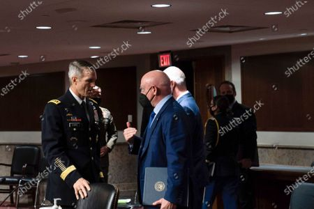 Sen. Mark Kelly, D-Ariz., speaks to Special Operations Command Gen. Richard Clarke after a hearing to examine United States Special Operations Command and United States Cyber Command in review of the Defense Authorization Request for fiscal year 2022 and the Future Years Defense Program, on Capitol Hill, in Washington
