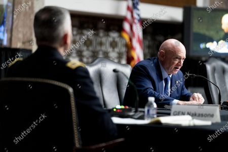 Cyber Command Commander, National Security Agency Director and Central Security Service Chief, Gen. Paul Nakasone, left, appears as Sen. Mark Kelly, D-Ariz., right, asks a question during a hearing to examine United States Special Operations Command and United States Cyber Command in review of the Defense Authorization Request for fiscal year 2022 and the Future Years Defense Program, on Capitol Hill, Thursday, March 25, 2021, in Washington.  Pool Photo by Andrew Harnik/UPI