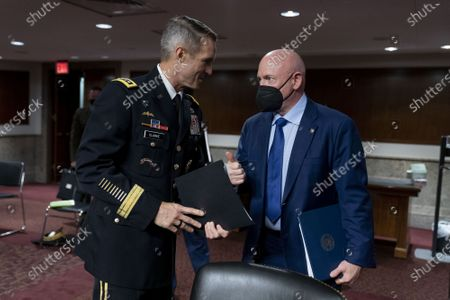 Special Operations Command Gen. Richard Clarke, left, and Sen. Mark Kelly, D-Ariz., right, speak following a hearing to examine United States Special Operations Command and United States Cyber Command in review of the Defense Authorization Request for fiscal year 2022 and the Future Years Defense Program, on Capitol Hill, Thursday, March 25, 2021, in Washington. Pool Photo by Andrew Harnik/UPI