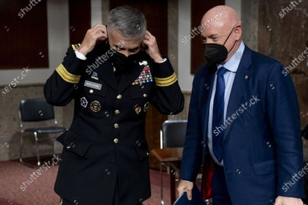 U.S. Cyber Command head, National Security Agency Director and Central Security Service Chief Gen. Paul Nakasone, left, and Sen. Mark Kelly, D-Ariz., right, speak following a hearing to examine United States Special Operations Command and United States Cyber Command in review of the Defense Authorization Request for fiscal year 2022 and the Future Years Defense Program, on Capitol Hill, Thursday, March 25, 2021, in Washington. Pool Photo by Andrew Harnik/UPI