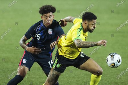 USA's Chris Richards, left, duels for the ball with Jamaica's Andre Gray during the international friendly soccer match between USA and Jamaica at SC Wiener Neustadt stadium in Wiener Neustadt, Austria