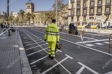 """A municipal worker is seen on Pelayo Street during the adaptation works for two new pedestrian lanes. The Barcelona City Council of the mayor Ada Colau applies """"emergency tactical planning"""" to recover for pedestrian use two of the vehicle lanes of the popular and commercial Pelayo street."""