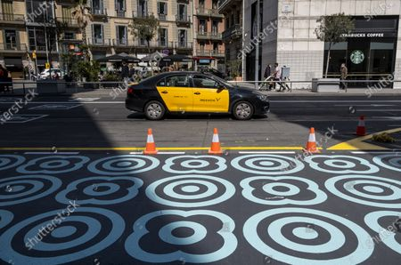 """The new decorative pattern painted in blue on the road is seen on Pelayo street during the adaptation works for two new pedestrian lanes. The Barcelona City Council of the mayor Ada Colau applies """"emergency tactical planning"""" to recover for pedestrian use two of the vehicle lanes of the popular and commercial Pelayo street."""