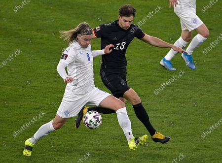 Iceland's Birkir Bjarnason, left, and Germany's Leon Goretzka challenge for the ball during the World Cup 2022 group J qualifying soccer match between Germany and Iceland in Duisburg, Germany