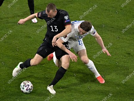 Germany's Lukas Klostermann, left, and Iceland's Jon Dadi Bodvarsson challenge for the ball during the World Cup 2022 group J qualifying soccer match between Germany and Iceland in Duisburg, Germany
