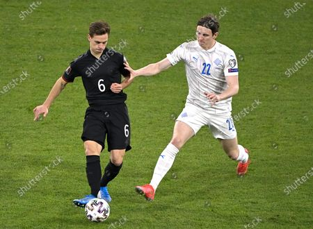 Germany's Joshua Kimmich, left, and Iceland's Jon Dadi Bodvarsson challenge for the ball during the World Cup 2022 group J qualifying soccer match between Germany and Iceland in Duisburg, Germany