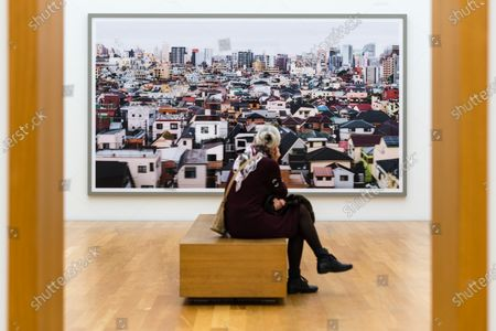 A visitor sits in front of the photographic work 'Tokyo' (2017) on display in the exhibition 'Andreas Gursky' at the Museum of Fine Arts Leipzig, in Leipzig, Germany, 25 March 2021. For the first time, the museum is showing an institutional solo exhibition of the German photographer and artist Andreas Gursky, featuring around 80 works, including around 50 large formats, in his native Leipzig.