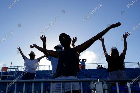 Stock Image of Socially distanced fans vie for an autographed ball after a tennis match between Aryna Sabalenka, of Belarus, and Tsvetana Pironkova, of Bulgaria, during the Miami Open tennis tournament, in Miami Gardens, Fla