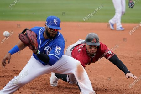 Kansas City Royals first baseman Carlos Santana, left, gets the throw before tagging out Arizona Diamondbacks' Tim Locastro, right, on a pickoff at first base during the third inning of a spring training baseball game, in Surprise, Ariz