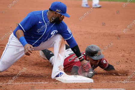 Kansas City Royals first baseman Carlos Santana, left, tags out Arizona Diamondbacks' Tim Locastro on a pickoff at first base during the third inning of a spring training baseball game, in Surprise, Ariz