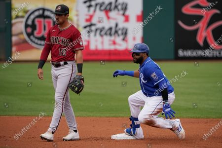 Kansas City Royals' Carlos Santana, right, slides into second base in front of Arizona Diamondbacks shortstop Josh Rojas (10) in the first inning of a spring training baseball game, in Surprise, Ariz