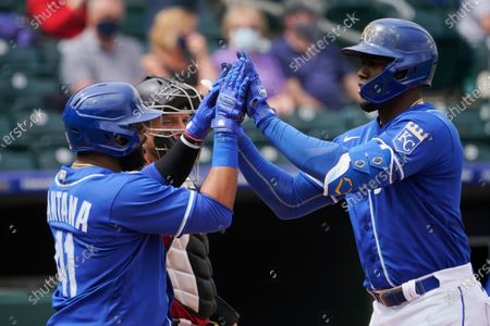 Kansas City Royals' Jorge Soler, right, celebrates with teammate Carlos Santana, left, in front of Arizona Diamondbacks catcher Stephen Vogt as he crosses home plate with a three-run home run during the first inning of a spring training baseball game, in Surprise, Ariz