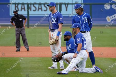 Kansas City Royals infielders, from left, Hunter Dozier, Carlos Santana, Whit Merrifield and Adalberto Mondesi watch during a pitching change in the fifth inning of a spring training baseball game against the Arizona Diamondbacks, in Surprise, Ariz