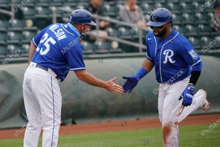 Kansas City Royals' Carlos Santana, right, slaps hands with third base coach Vance Wilson, as he rounds third base on a home run in the fifth inning of a spring training baseball game against the Arizona Diamondbacks, in Surprise, Ariz