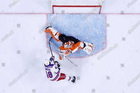 New York Rangers' Brendan Lemieux, left, cannot get a shot past Philadelphia Flyers' Brian Elliott during the third period of an NHL hockey game, in Philadelphia