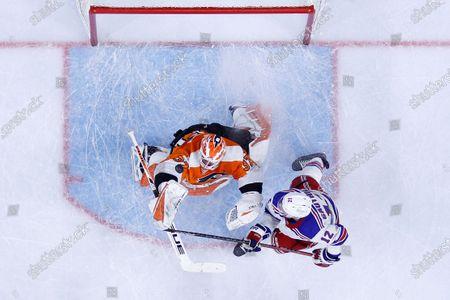 Philadelphia Flyers' Brian Elliott, left, battles for the puck against New York Rangers' Julien Gauthier during the third period of an NHL hockey game, in Philadelphia