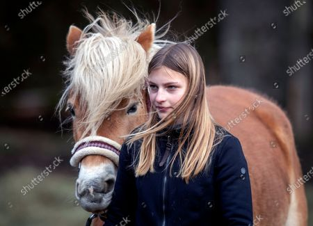 13-year-old daughter Anni walks next to her Haflinger horse in Eisemroth, central Germany, . One year into the coronavirus pandemic, Katja Heimann is still trying to keep her spirits up - despite several lockdowns and months of teaching seven of her children in home schooling