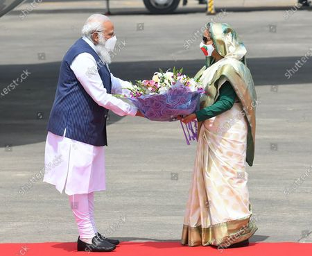 In this photo provided by Prime Minister of India Narendra Modi's twitter handle, Indian Prime Minister Narendra Modi receives a bouquet of flowers from Bangladesh's Prime Minister Sheikh Hasina in Dhaka, Bangladesh, . Modi arrived in Bangladesh's capital on Friday to join celebrations marking 50 years of the country's independence, but his trip was not welcomed by all. The two-day visit, his first foreign trip since the coronavirus pandemic began last year, will also include joining commemorations for 100 years since the birth of independence leader Sheikh Mujibur Rahman, the father of current Prime Minister Sheikh Hasina