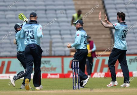 England's Reece Topley, right, celebrates with teammates the dismissal of India's Shikhar Dhawan during the second one-day international cricket match between India and England in Pune, India