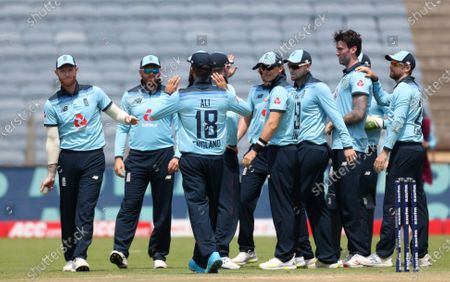 England's Reece Topley, without cap, celebrates with teammates the dismissal of India's Shikhar Dhawan during the second one-day international cricket match between India and England in Pune, India