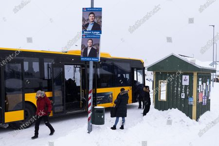 People walk under campaign posters of Steen Lynge (top), the Greenlandic Minister of Foreign Affairs and Energy, and Jens-Frederik Nielsen (bottom), Minister of Industry and Business and Mineral Resources, both from Democrats Party, in Nuuk, Greenland, 25 March 2021. Greenland will hold parliamentary elections on 06 April 2021.