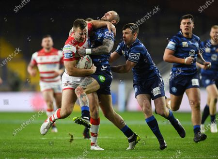 Stock Photo of Iain Thornley of Leigh Centurions is tackled by Zak Hardaker and Harry Smith of Wigan Warriors