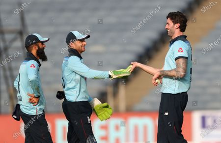 England's Reece Topley, right, celebrates with teammates the dismissal of India's Hardik Pandya during the second One Day International cricket match between India and England at Maharashtra Cricket Association Stadium in Pune, India