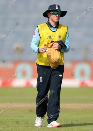 England's injured captain Eoin Morgan carries a bag as he walks into the field during the second One Day International cricket match between India and England at Maharashtra Cricket Association Stadium in Pune, India