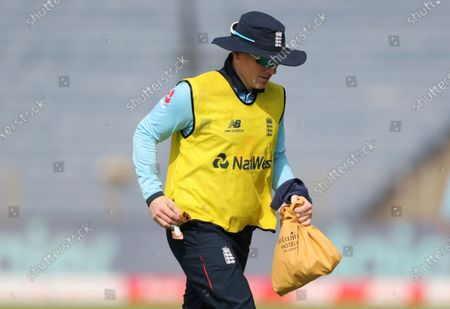 England's injured captain Eoin Morgan carries a bag as he runs off the field at drinks break during the second One Day International cricket match between India and England at Maharashtra Cricket Association Stadium in Pune, India