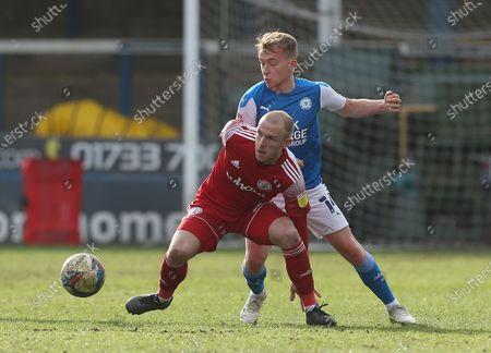 Peterborough's Louis Reed battles with Accrington Stanley's David Morgan